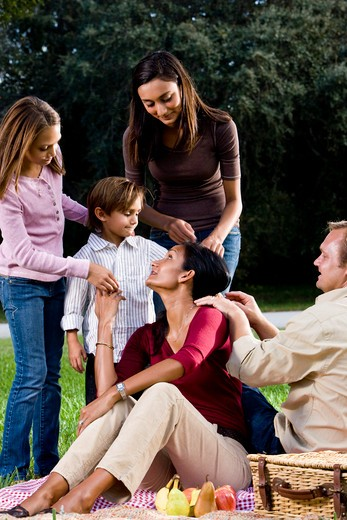 Interracial family of five having picnic in park : Stock Photo