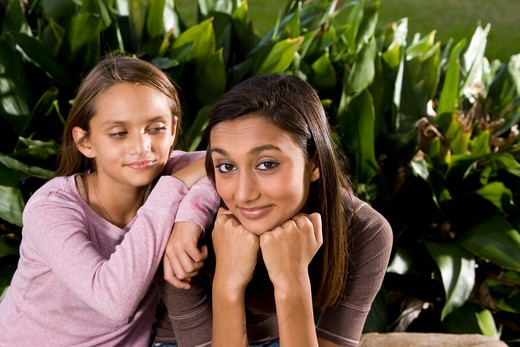 Pretty mixed-race Indian teenage girl with younger sister : Stock Photo