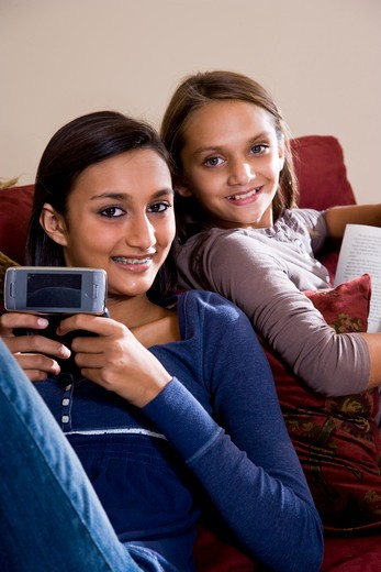 Sisters relaxing together at home on sofa : Stock Photo