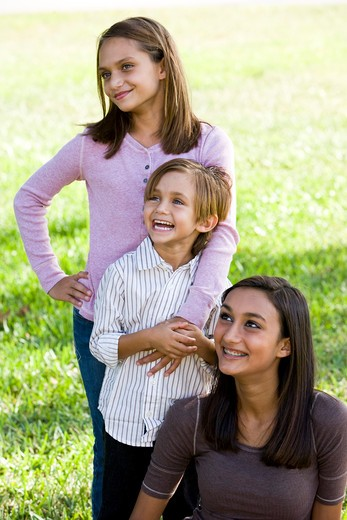 Stock Photo: 4172R-1825 Three close siblings together outdoors on sunny day