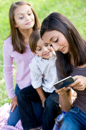 Teenage girl showing mobile phone to younger siblings : Stock Photo