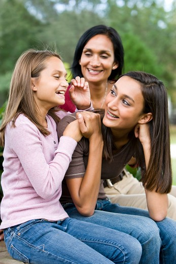 Affectionate mother and two daughters laughing together : Stock Photo