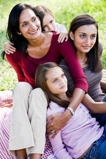 Happy mother with three beautiful children sitting together : Stock Photo