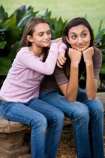 Stock Photo: 4172R-1860 Affectionate sisters sitting together on bench