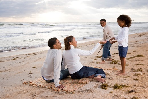 Stock Photo: 4172R-1881 Happy African-American family playing on beach