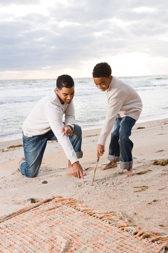 Stock Photo: 4172R-1885 African-American father and son playing on beach