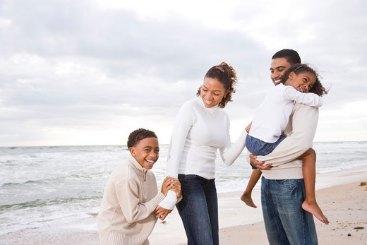Stock Photo: 4172R-1899 Happy African-American family of four on beach