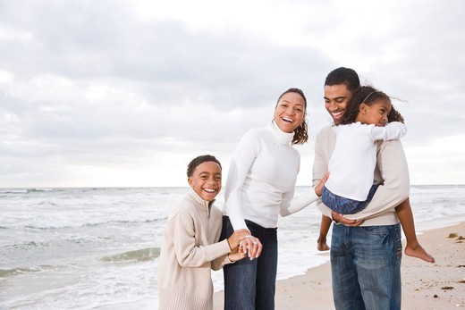 Happy African-American family of four on beach : Stock Photo