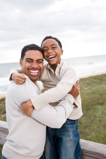 African-American father and son laughing at beach : Stock Photo