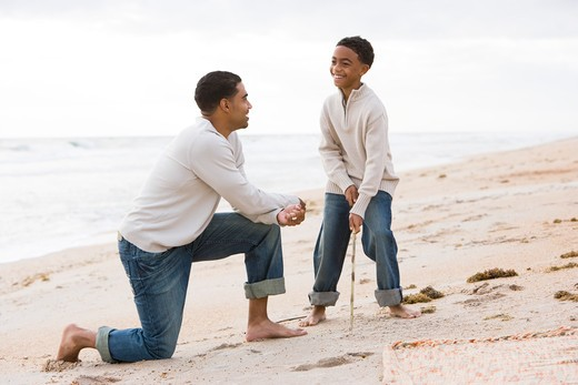 African-American father and son playing on beach : Stock Photo