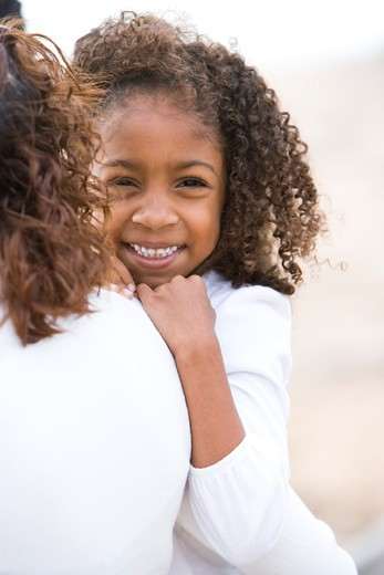 Close-up of cute African-American girl in mother's arms : Stock Photo