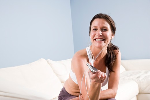 Woman listening to mp3 player with earbuds : Stock Photo