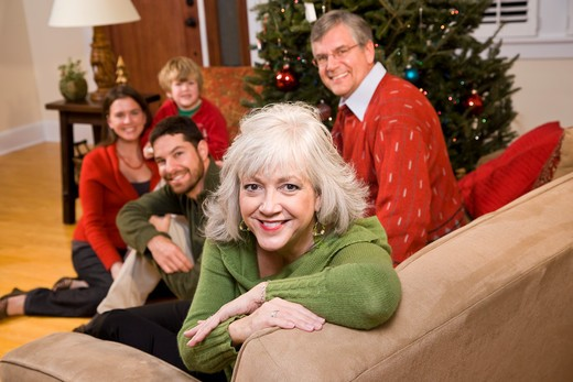 Senior woman with family by Christmas tree : Stock Photo