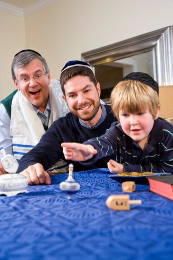 Boy with father and grandfather spinning dreidel : Stock Photo