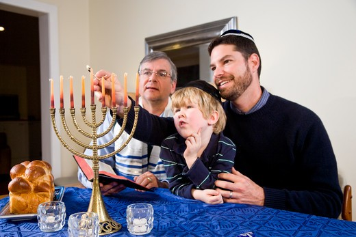 Stock Photo: 4172R-2053 Jewish family lighting Chanukah menorah