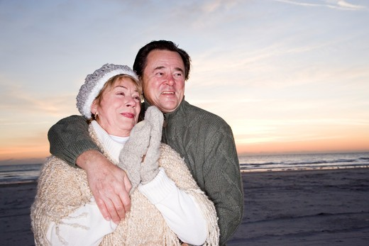 Affectionate senior couple in sweaters on beach : Stock Photo
