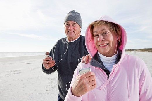 Senior couple listening to music on MP3 player : Stock Photo