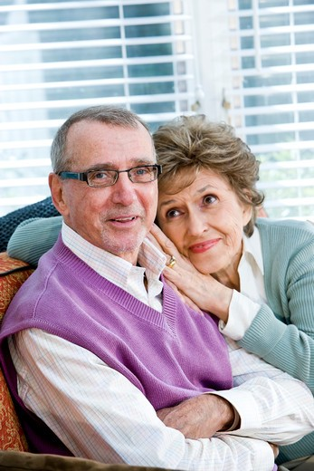 Loving senior couple sitting together on couch : Stock Photo