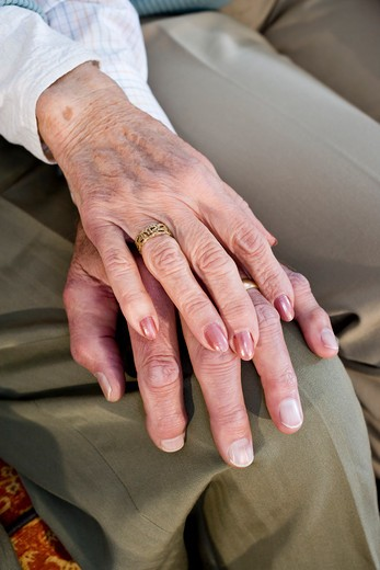 Close-up hands of senior couple resting on knee : Stock Photo