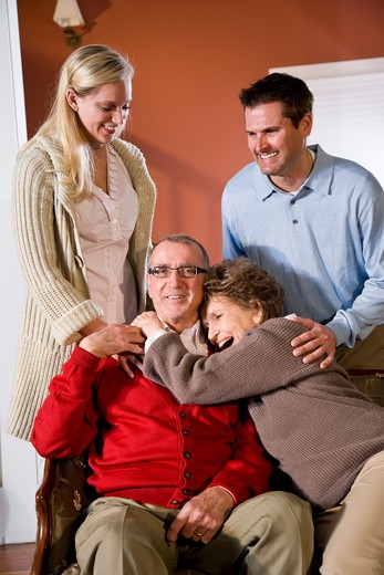 Senior couple at home on sofa with adult children : Stock Photo