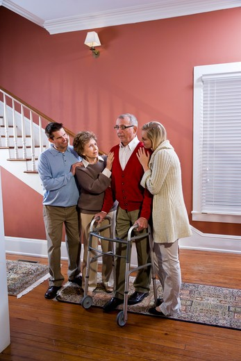 Elderly couple at home with adult children : Stock Photo