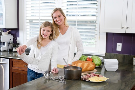 Mother and daughter in kitchen making lunch : Stock Photo