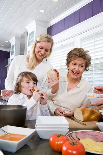 Three generation family in kitchen eating lunch : Stock Photo