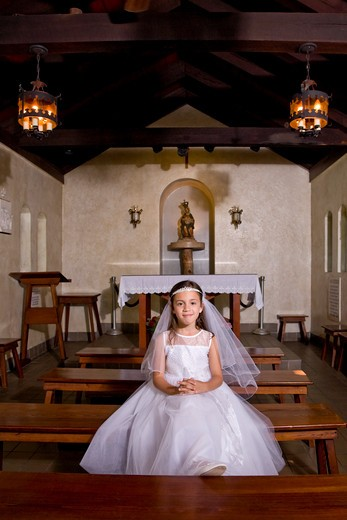 Young girl in church wearing first communion dress : Stock Photo