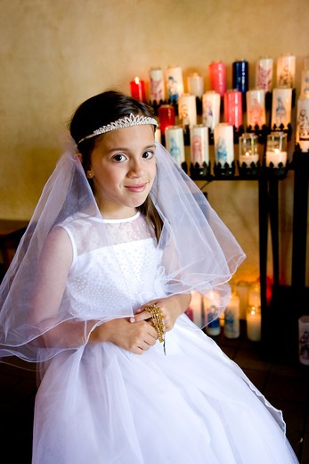Young girl wearing white dress holding rosary : Stock Photo