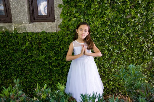 Beautiful child in white dress by ivy-covered wall : Stock Photo