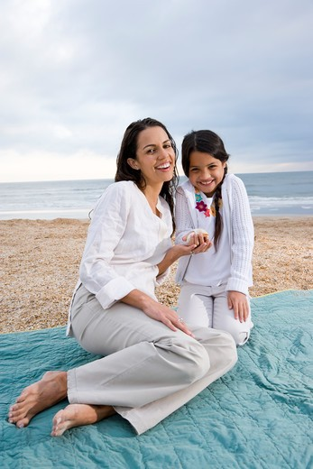 Hispanic mother and girl sitting on blanket at beach : Stock Photo