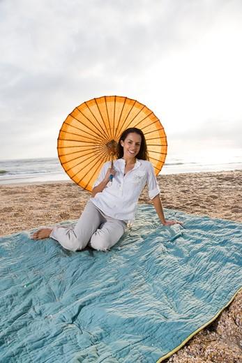 Hispanic woman with parasol on beach blanket : Stock Photo