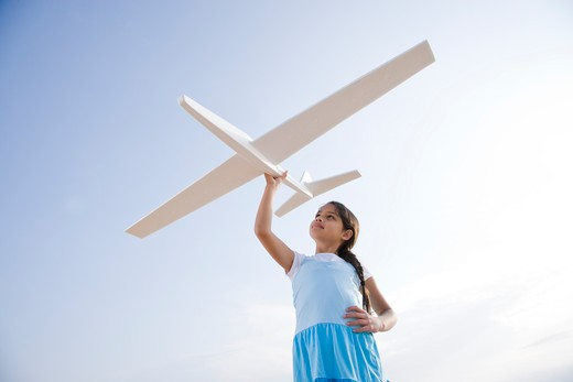 Pretty girl playing with toy glider : Stock Photo