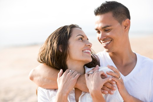 Close up of affectionate Hispanic couple on beach : Stock Photo