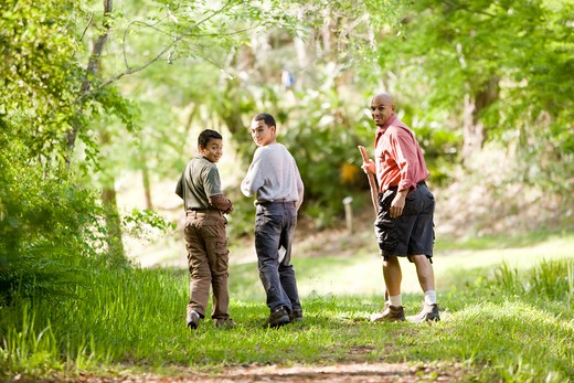 Hispanic father and sons hiking on trail in woods : Stock Photo