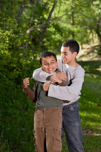 Stock Photo: 4172R-2414 Teenage boy playing with and teasing brother