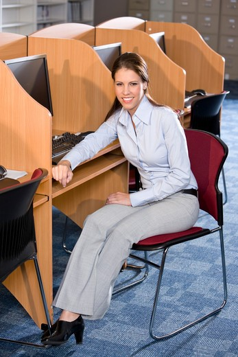 University student sitting at computer in library : Stock Photo