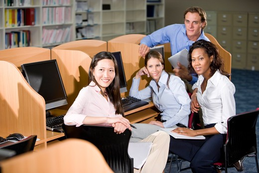 University students sitting  at library computer : Stock Photo