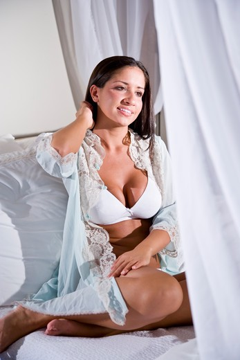 Young Hispanic woman sitting on white canopy bed : Stock Photo