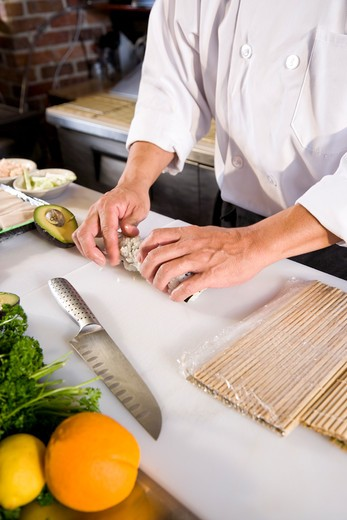 Stock Photo: 4172R-2585 Japanese chef in restaurant making sushi roll