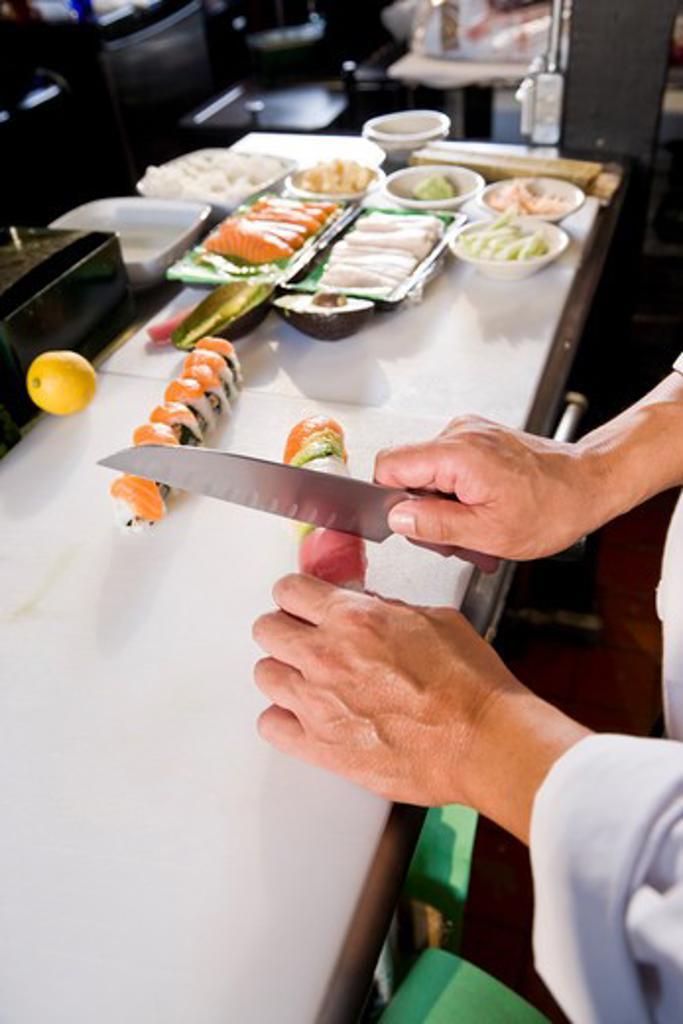Stock Photo: 4172R-2588 Chef in Japanese restaurant preparing sushi rolls