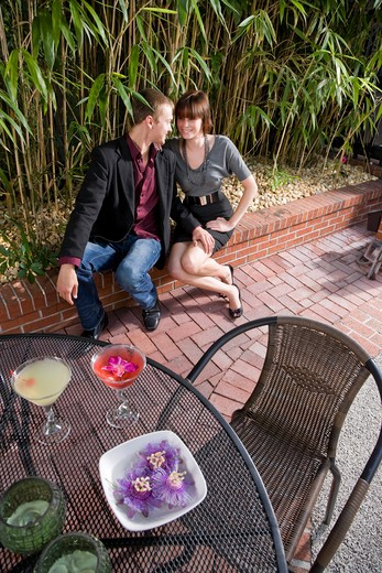 Young romantic couple having drinks on patio : Stock Photo