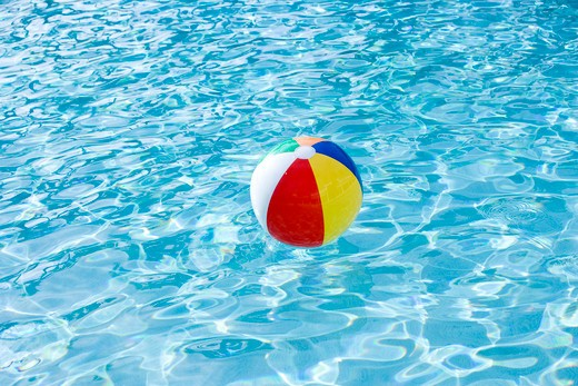 Beach ball floating on surface of swimming pool : Stock Photo