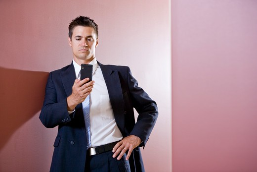 Businessman in suit texting in hallway : Stock Photo