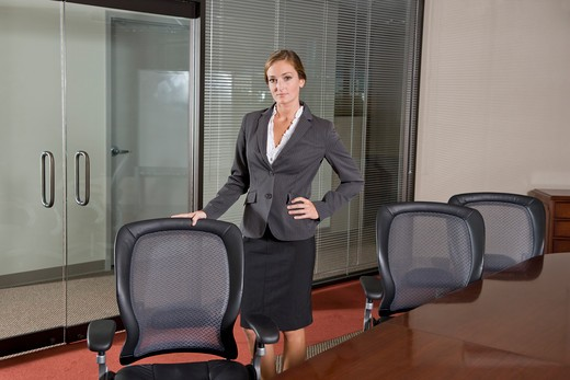 Female office worker standing in boardroom : Stock Photo