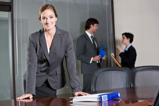 Confident businesswoman, colleagues in background : Stock Photo