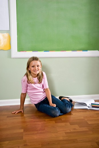 Child with books sitting on floor by blackboard : Stock Photo