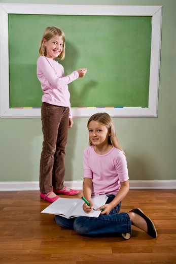 Stock Photo: 4172R-2759 Girls writing on blackboard and doing homework