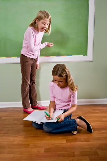 Girls writing on blackboard and doing homework : Stock Photo