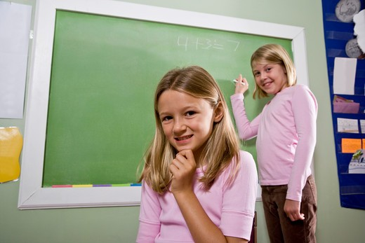 Girls writing on blackboard in classroom : Stock Photo
